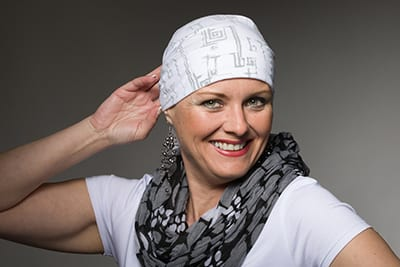 Portrait of beautiful positive smiling middle age woman patient with cancer wearing headscarf, hope in healing