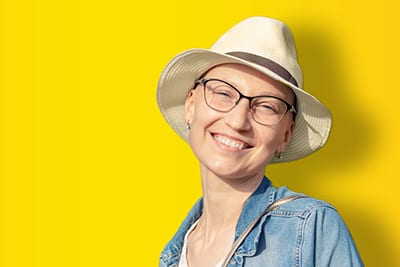 Happy young caucasian bald woman in hat and casual clothes enjoying life after surviving breast cancer. Portrait of beautiful hairless girl smiling isolated on golden yellow background.