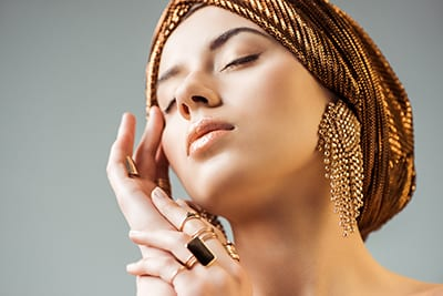 young naked woman with closed eyes, shiny makeup, golden rings and earrings in turban isolated on grey